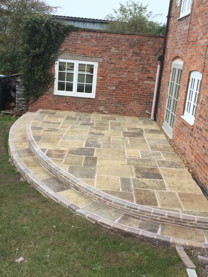 A riven Yorkstone paver patio in a semi circular shape